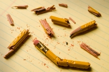 Broken pencil fragments on yellow paper | Shattered pencil fragments on a yellow legal pad, perhaps symbolizing writer's block